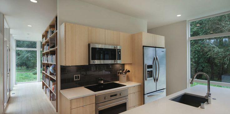 moderna cocina con gabinetes de madera clara y electrodomésticos de acero inoxidable