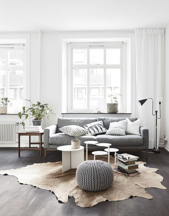 Scandinavian living room. Super minimalist with low-profile furniture and decor, accentuating the windows, curtains, and ceiling.