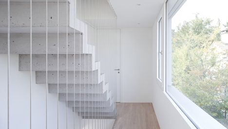 Concrete house in Switzerland by Basel studio on3 architekten has gabled end walls that appear folded along central vertical seams.          An exposed concrete staircase connects the three storeys of Wohnhaus Ginkgo and is suspended behind a balustrade of taught wires between the two upper floors.        A large dormer window increases the amount of
