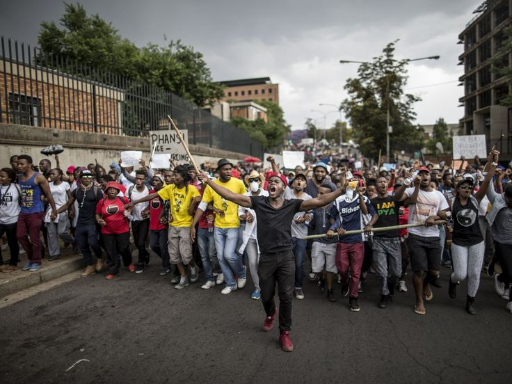 Students march through the campus of the University of the Witwatersrand in Johannesburg during a protest against fee hikes. Universities in Cape Town, Johannesburg, Pretoria and other cities have halted lectures during several days of protests against fee increases that many students say will force poor blacks further out of the education system.  Marco Longari, AFP/Getty Images