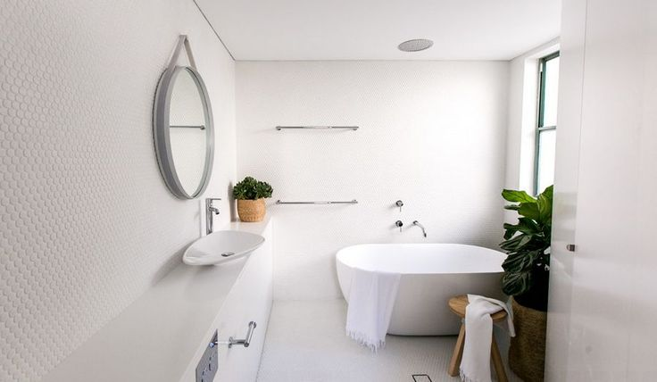 Contemporary white bathroom with penny tiles on wall and freestanding tub
