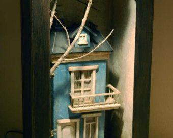 Diorama di casa di legno di colore blu. Motif originale in legno e argilla. Ha interni luce visibile attraverso le finestre. Dimensioni approssimano di 46 cm. x 25 alta cm di larghezza e 13,5 cm di profondità. Scatola marrone scuro colore esterno. Colore marrone del rotto, luce colori blu, neri, bianchi e fango. Pezzo unico realizzato a mano.