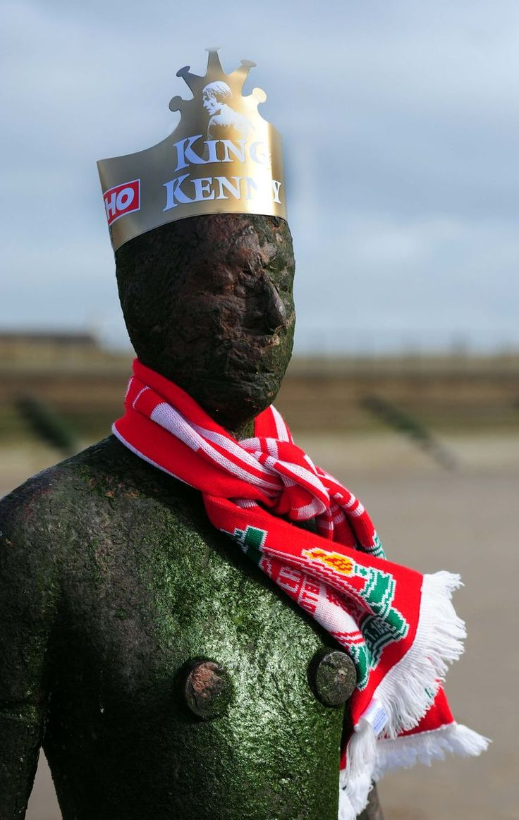 Liverpool Echo's King Kenny paper crowns on one of the Ironmen statues at Crosby beach