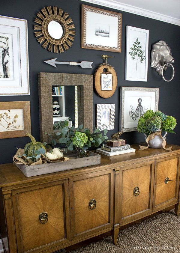 Art collage on dark charcoal walls | console decorated with pumpkins and fall flowers | Post includes link to tips on how to create your own gallery wall!