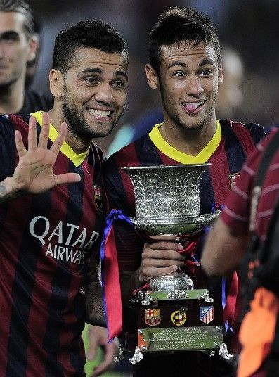 Dani Alves(L) and Neymar da Silva Santos Junior(R) of FC Barcelona celebrate after winning the Spanish Supercup against Atletico Madrid at the Camp Nou stadium in Barcelona, Spain, 2013