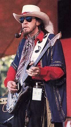 Stevie Ray Vaughan. Just when I thought he couldn't be any more of a bad ass, I stumble across this pic. Beard, pipe, and laying the whoop-ass on the guitar!