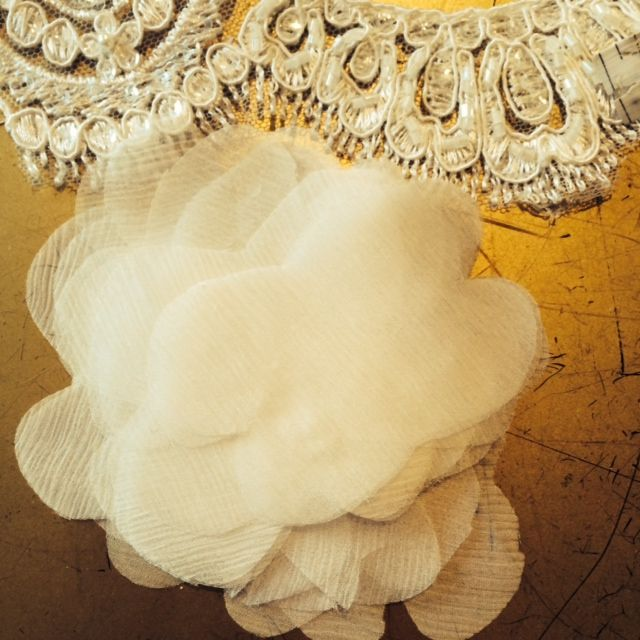 Exquisite, scalloped lace and a handmade fabric flower.