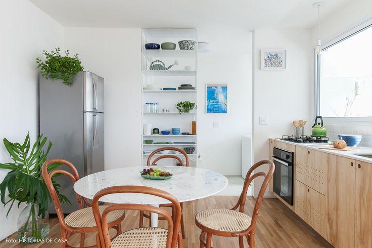 Cozinha minimalista tem marcenaria feita com compensado, cadeiras thonet e mesa saarinen.