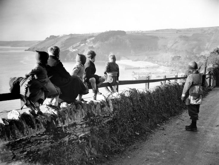 French children watch the landing of American troops from landing craft, unidentified location, probably Normandy, 1944.