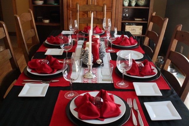 Black and white and red table settings for Christmas Eve Feast. Poinsettia fo...