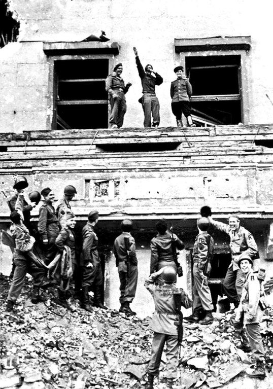 Allied (British, American, Soviet) soldiers mock Hitler atop his balcony at the Reich Chancellery, 1945.