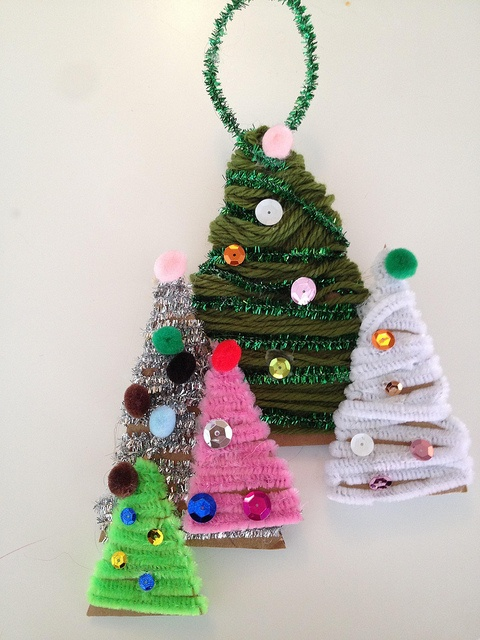 Idea for homemade ornaments. Christmas trees made by wrapping cardboard with yarn, pipecleaners, etc. Decorate.