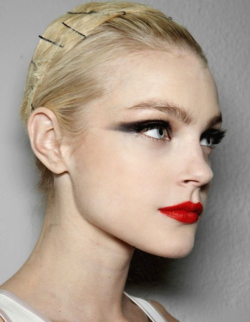 Bold, dark eyeshadow and mascara, smudged outward, plain waterline with a slight brush of rose shadow, bright red matte lips.