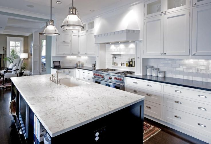 Gorgeous slab granite and transitional pendant light fixtures highlight this fabulous kitchen.