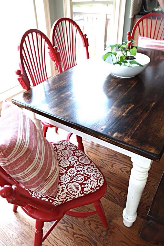 Two toned farmhouse table with classic red chairs.