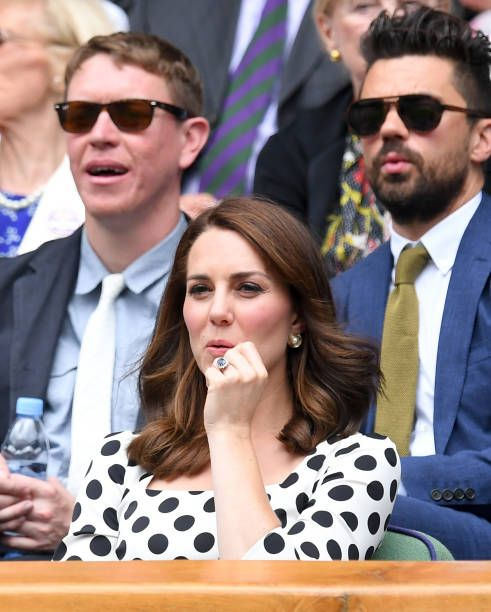 Catherine Duchess of Cambridge and actor Dominic Cooper react as they attend the opening day of Wimbledon 2017 on July 3 2017 in London England