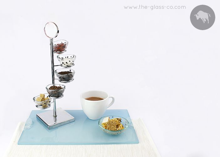 A metal stand with small glass bowls for sugar and cookies on a light blue glass tray for coffee or tea presentation designed by Glass Studio www.the-glass-co.com