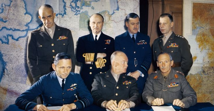General Dwight D. Eisenhower is shown with his staff. L to R, seated: Air Chief Marshall Sir Arthur Tedder, General Eisenhower and General Sir Bernard Montgomery. L to R, standing: Lieutenant General Omar Bradley, Admiral Sir Bertram Ramsey, Air Chief Marshal Sir Trafford Leigh Mallory and Lieutenant General W. Bedell Smith.