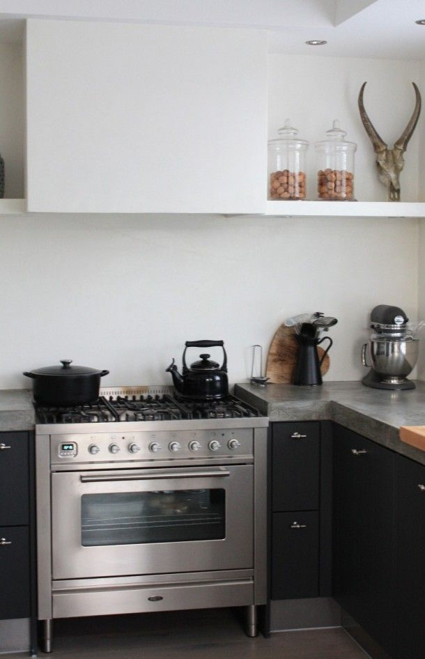 compact black kitchen with concrete countertop