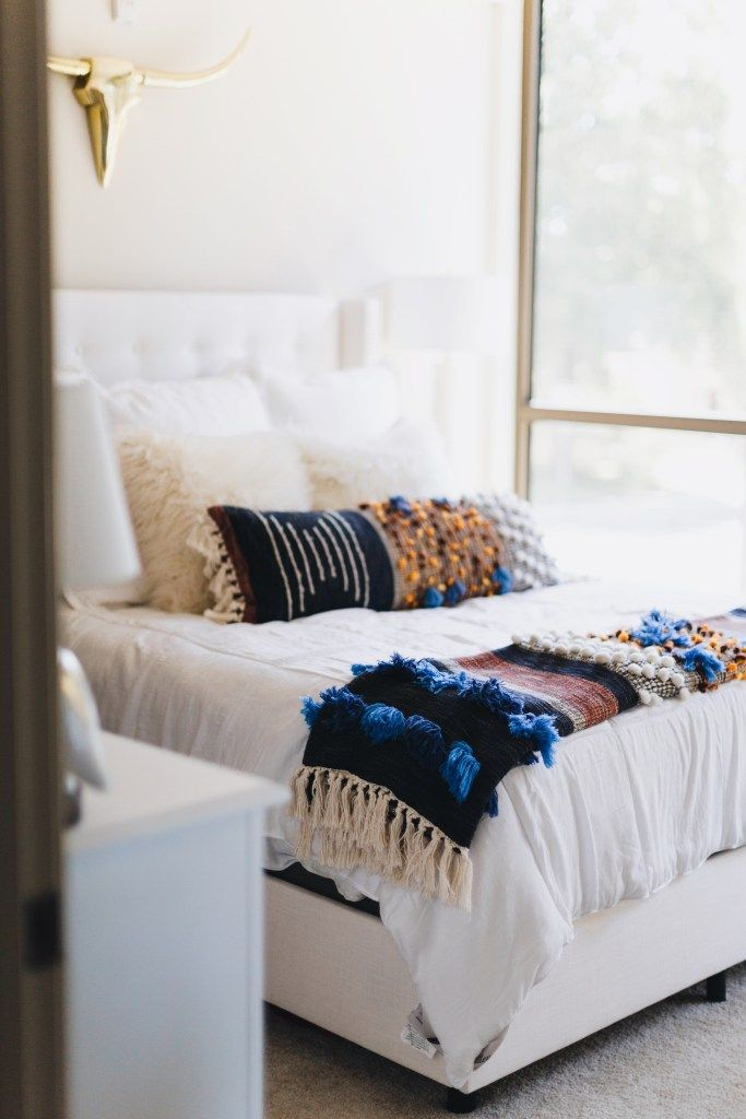 white walls, white upholstered bed, colourful ethnic bedding