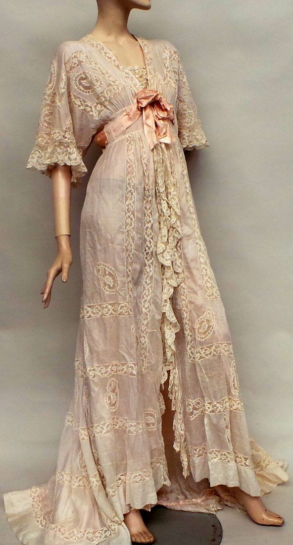 c1900 negligee of creamy muslin and lace which fastens at the bodice with tiny mother of pearl buttons. The robe falls from the empire line to a longer train at the back and has a silk satin bow at the bust. The garment is lined with fine pale pink silk.                                                                                                                                                      More