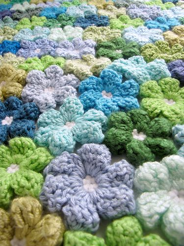 """crochet flower blanket. From the comments: """"Well, I made up this pattern myself, so It's not written anywhere. Since 7 different people did it together, we made every flower separately, and then attached them with another row of s.c. If only one person is making it - you can attach the flower as you make it, by making a slst at the top of the leaf into the other flowers."""""""
