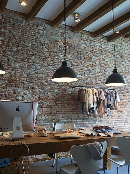 Beautiful urban living: exposed brick wall and industrial lights juxtaposed by solid wood beams and table. The whole look is softened by clothing hanging on the exposed rail.