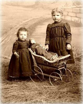 Late Victorian/Edwardian photo of two siblings with their doll and pram set against the backdrop of an English country scene.