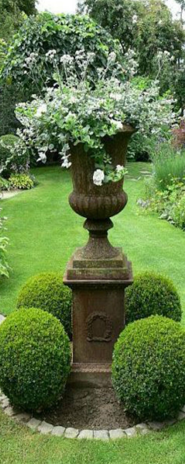 love the use of elevated garden urns surrounded by potted shrubs to create a garden / square effect.