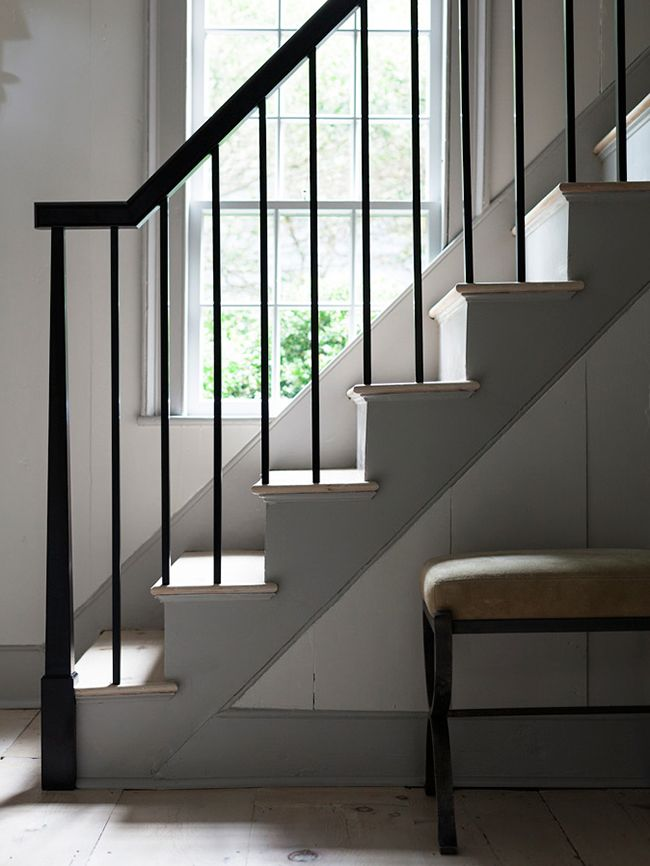 The slight triangular shape of the newel post is so subtle and elegant. It's the perfect staircase update to compliment this historical East Coast cottage. Darker gray trim, light gray walls and black banister in the stairway. | Steven Gambrel's Latest Sag Harbor Project