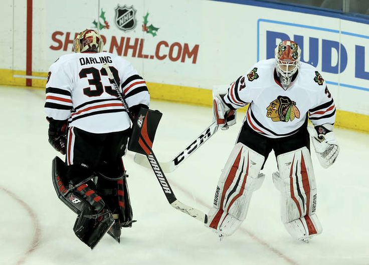NEW YORK, NY - DECEMBER 13: Scott Darling #33 and Lars Johansson #31 of the Chicago Blackhawks change places during warm ups before the game against the New York Rangers on December 13, 2016 at Madison Square Garden in New York City. (Photo by Elsa/Getty Images)