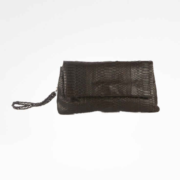 Kalimatan  Slither into style this season with this oversize phyton clutch. Remaining chic and elegant, this clutch will add a twist to any outfit. Functional and capacious. With zip. Designed for a naturally stylish clientele for whom the handbag is not merely an accessory but a projection and confirmation of her own image.