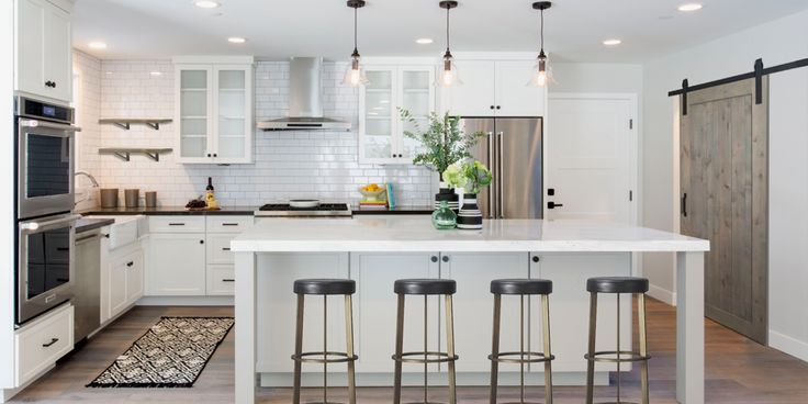 White Subway tile and Shaker cabinets offsets the floating open shelf while complementing the white marble island. Antique black hardware coupled with a wooden barn door for the pantry grounds this airy design. https://ecomindedsolutions.com/project/cedros-design-district/