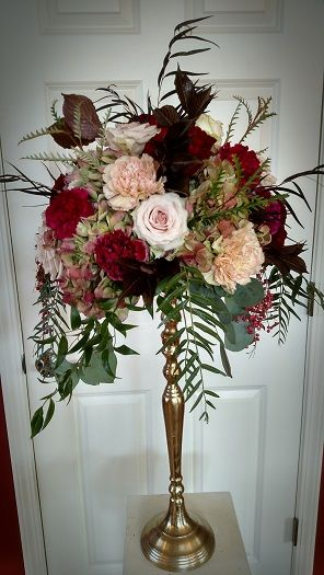 #tallcenterpiece Tall centerpiece arrangement on our antique gold stands with antique green hydrangeas, blush and burgundy blooms and assorted greens.