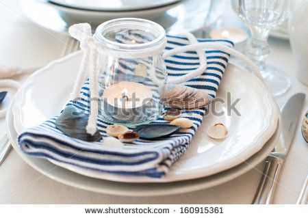 Table setting in maritime style, with candles, sea shells and striped napkins, close up - stock photo