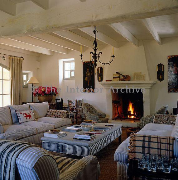 Il salotto rustico imbiancata è arredato con comodi divani e sedie rivestite in un tessuto a righe