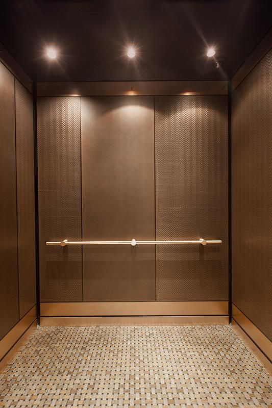 LEVELe-101 Elevator Interior with customized panel layout; panels in Bonded Bronze with Dark Patina and Mazatlán pattern, Bonded Bronze with Dark Patina and custom pattern; Compass handrail in Satin Bronze at Residences at the InterContinental, Boston, Massachusetts