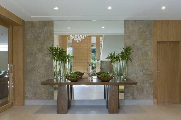 Neste projeto a arquiteta Debora Aguiar usa espelhos para ampliar o ambiente no Hall.