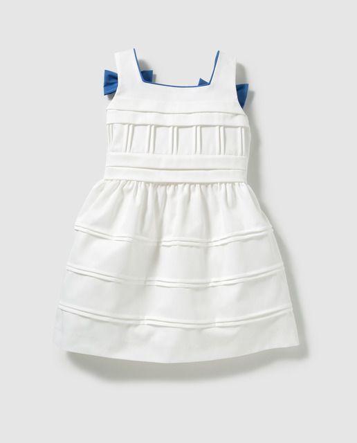 Vestido en color blanco, con tirante ancho y adorno de lazo en azulón. Lleva el cierre en la espalda mediante dos botones, forro interior a tono y abertura.