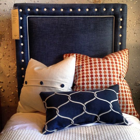 A preppy but polished take on dressing up a twin bed at Century. Deep navy lined padded headboard with white welt and button nailhead trim, mixed with textural, patterned bedding. Century, Market Square 5th Floor