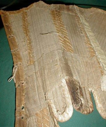 """Stays, Ebay Auction c.2004  This is a rare 1740-1760 early American colonial time period corset/stays. Made of two tone tan linen that is laid over what is probably rows of cane that are tightly hand stitched into place. A band of thin cotton extends down the front seam. The top edge and bottom hem and flaps are lined with kid leather. The inside is lined with heavy tan homespun linen. Bust 34"""". Waist 26"""". Front length 12"""". Back length 13.5""""."""