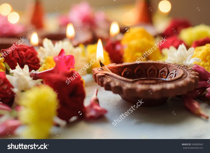 stock-photo-diya-lamps-lit-during-diwali-celebration-with-flowers-and-sweets-in-background-334000943.jpg (1500×1096)