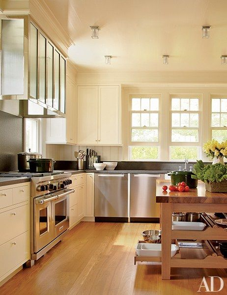 The black-granite counters and backsplashes offset the kitchen's white cabinetry | archdigest.com