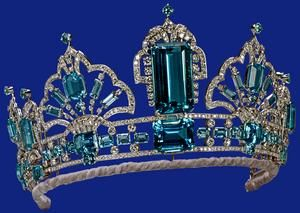 Emerald Tiara, Britain. When first made in 1957, the tiara consisted of the three upright rectangular stones (detachable for use as brooches), mounted on a simple platinum band. The large central stone was originally the pendant of the necklace given to The Queen by the President and People of Brazil in 1953 as a Coronation present. In 1971 the tiara was adapted to take four scroll ornaments from an aquamarine and diamond jewel given to The Queen by the Governor of São Paulo in 1968.