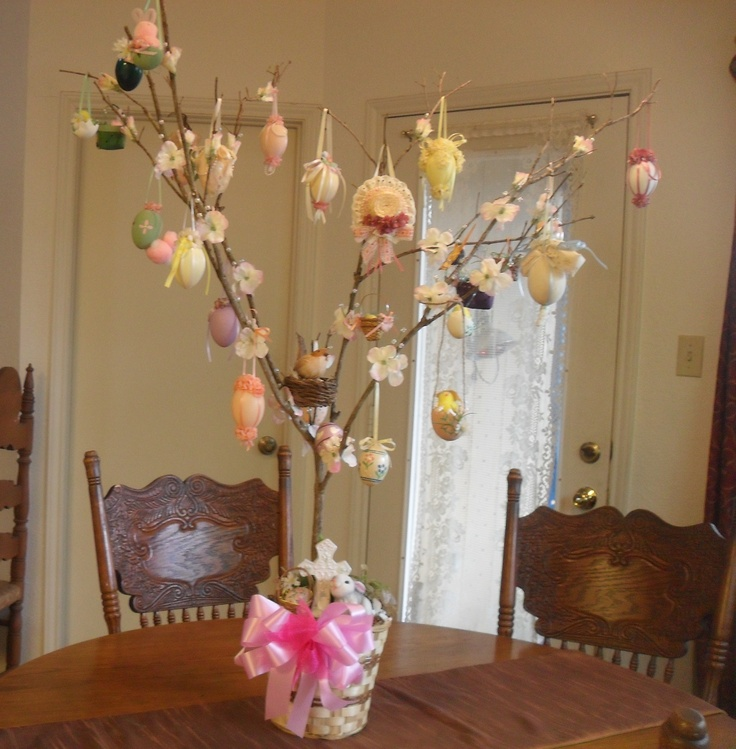 Easter Tree:  Celebrating the beauty of Easter and spring with a tree full of decorations for display. A basket with an inner pot of spring foliage planted in it holds a porcelain cross amidst hidden Easter eggs, a bunny, an Easter basket and spring flowers. Handmade decorations of Easter eggs, baskets, a bonnet, birds, butterflies, baby chicks and bunnies hang from the flower covered branches. Easter's promises of new life & new growth resonate and gives a cheery addition to my home.