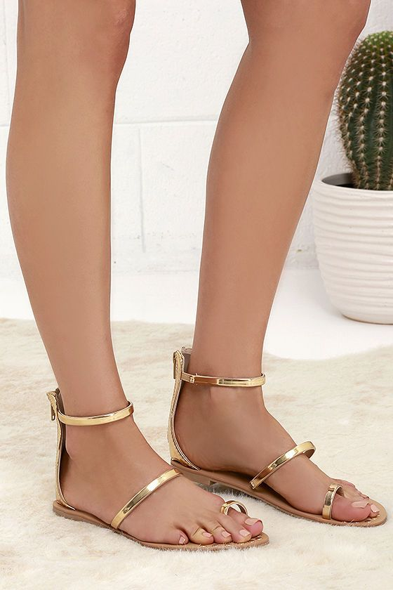 """We definitely have a weakness for the Achilles Gold Flat Ankle Strap Sandals! Three metallic gold bands include a toe loop and ankle strap, while gold studs along the footbed lend a decorative touch. 4"""" heel zipper."""