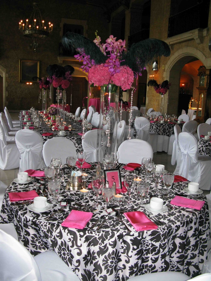 Tall centerpieces by Willow Haven including hot pink hydrangea, black ostrich feathers, pink orchids, and hanging crystals both inside and outside the cylindrical glass vases.