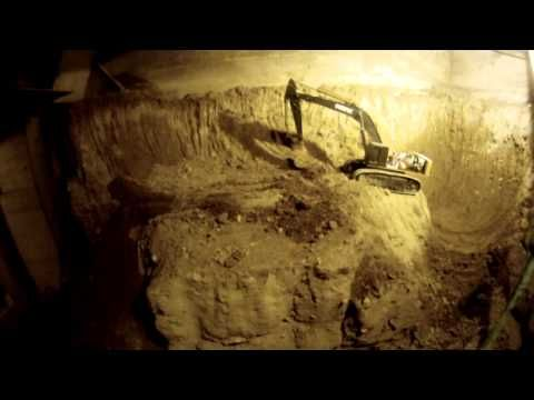 Guy digging out his basement using RC digging equipment since 1997. It's an obsession. But a really cute obsession.