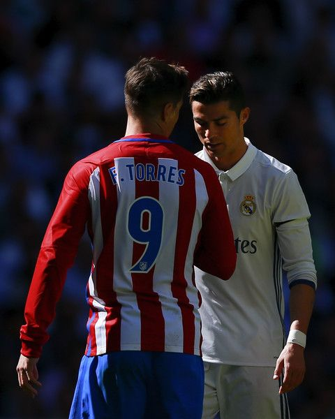 Cristiano Ronaldo (R) of Real Madrid CF reacts as Fernando Torres (L) of Atletico de Madrid speaks to him during the La Liga match between Real Madrid CF and Club Atletico de Madrid at Estadio Santiago Bernabeu on April 8, 2017 in Madrid, Spain.
