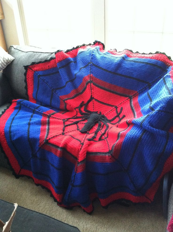 Crocheted Spiderman blanket with the symbol in the middle.